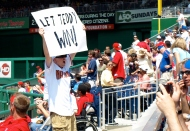A member of the Nat Pack holds up a sign reading Let Teddy Win at Nationals Park