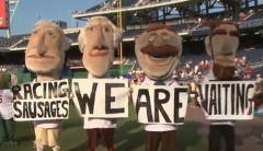 The Washington Nationals Presidents racing presidents hold up signs taunting the Milwaukee Brewers racing sausages